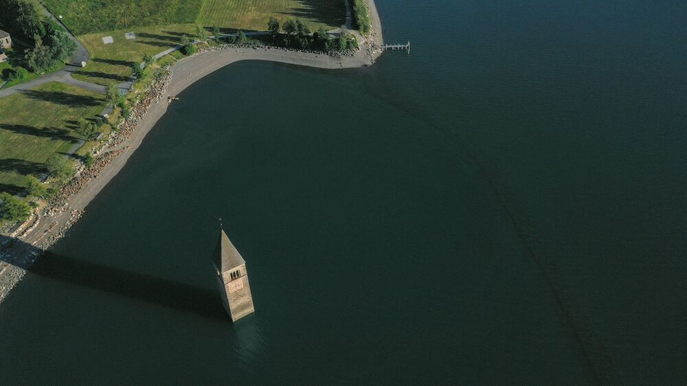 An aerial picture taken on 9 July 2020 in the new city of Curon Venosta (Graun im Vinschgau), about 100km north-west of Bolzano, northern Italy, shows the bell tower of Curon's old church poking above the surface of lake Resia. The church and village were submerged in 1950 as an artificial lake was created to power a hydroelectric plant.