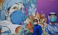 A man wearing a face mask walks in front of a mural at the Leishenshan Hospital that had offered beds for coronavirus patients in Wuhan, in China's central Hubei province on April 11, 2020