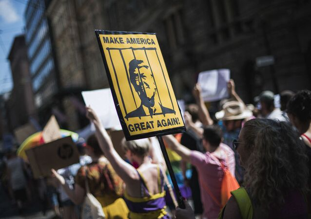 A protester holds a placard featuring US President Donald Trump behinid bars during the so-called Helsinki Calling march towards the Senate Square to defend the human rights, freedom of speech and democracy on July 15, 2018