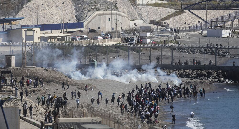 Spanish security forces throw tear gas at migrants attempting to cross the fence of the Spanish enclave of Ceuta