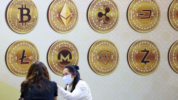 Customers talk against a backboard with signs of cryptocurrency during 2020 Taipei International Finance Expo in Taipei, Taiwan, November 27, 2020. REUTERS/Ann Wang/File Photo - Sputnik International