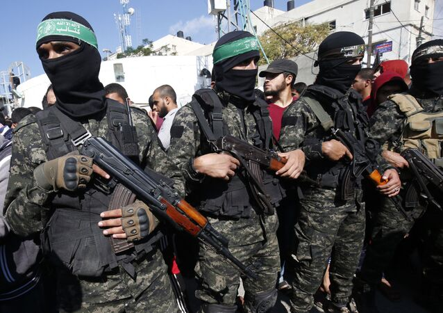 Palestinian militants of the Islamist movement Hamas' military wing Al-Qassam Brigades, attend the funeral of seven Palestinians, killed during an Israeli special forces operation in the Gaza Strip, on November 12, 2018, in Khan Younis
