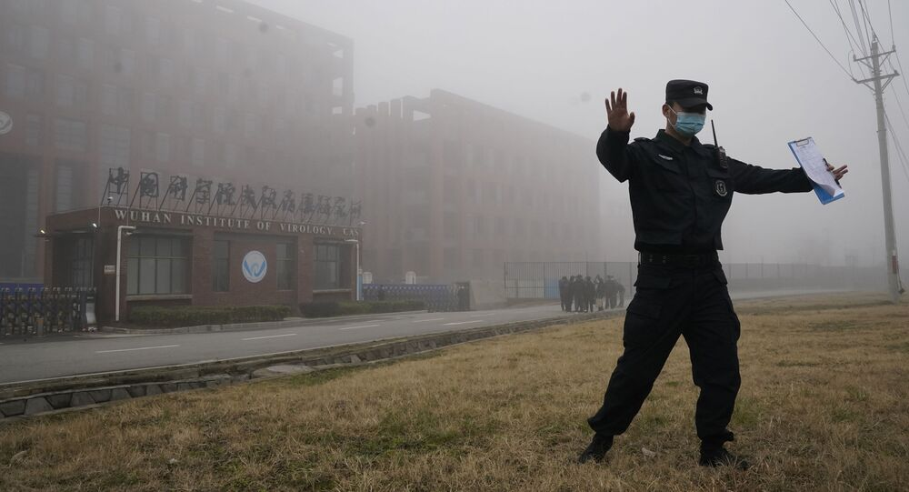 A security official moves journalists away from the Wuhan Institute of Virology after a World Health Organization team arrived for a field visit in Wuhan in China's Hubei province on Wednesday, Feb. 3, 2021
