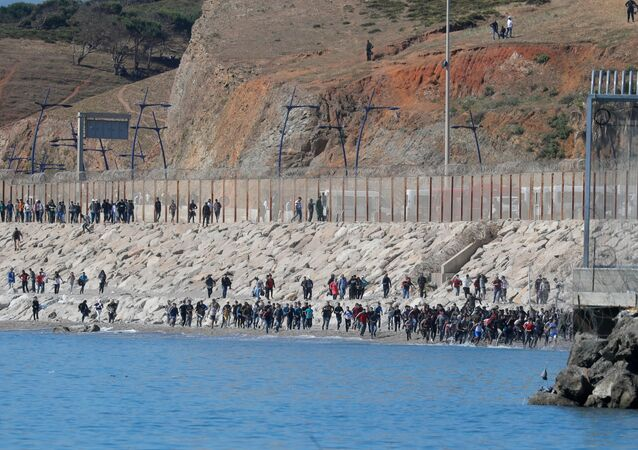 Migrants run towards the fence separating Morocco from Spain, after thousands of migrants swam across the border, in Ceuta, Spain, May 19, 2021. REUTERS/Jon Nazca