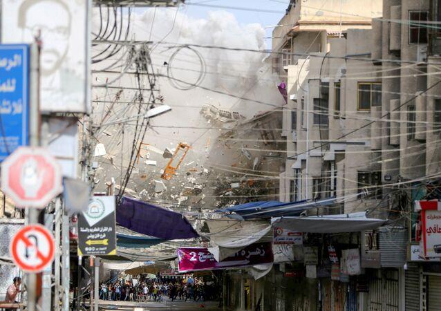 Debris fly as smoke rises following an Israeli air strike, amid Israeli-Palestinian fighting, in Khan Younis in the southern Gaza Strip, May 20, 2021. REUTERS/Ibraheem Abu Mustafa