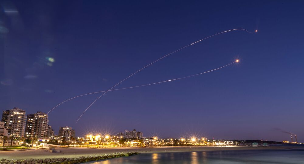 Streaks of light are seen as Israel's Iron Dome anti-missile system intercept rockets launched from the Gaza Strip towards Israel, as seen from Ashkelon, 19 May 2021