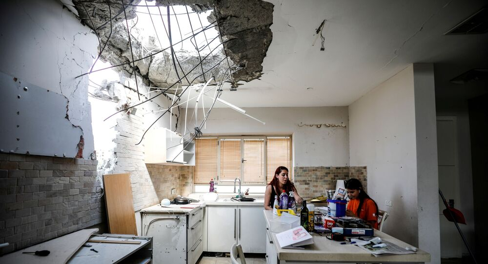 Family members of the Vaizel family, sit in the kitchen of their house which was damaged after it was hit by a rocket launched from the Gaza Strip earlier this week, in Ashkelon, Israel May 20, 2021