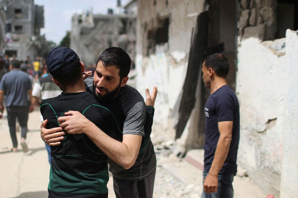 Palestinians hug each other after returning to their destroyed houses following the Israel-Hamas truce, in Beit Hanoun in the northern Gaza Strip.