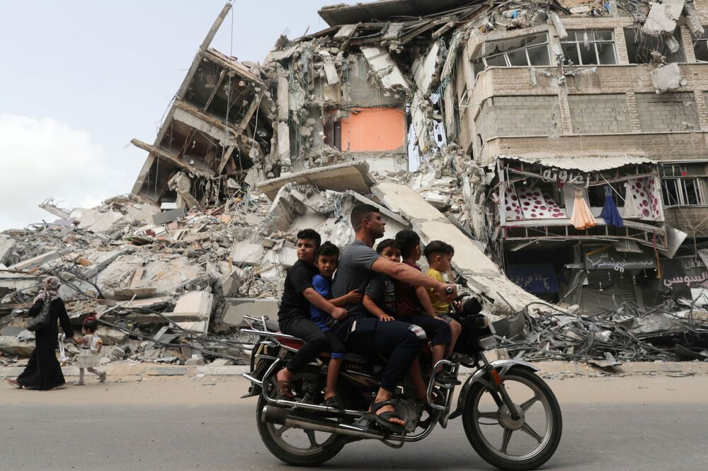 Palestinians ride a motorcycle past the site of an Israeli airstrike, following the Israel-Hamas truce.