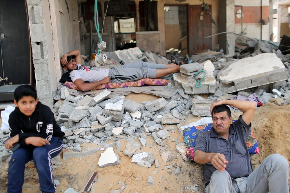 Palestinians rest after returning to their damaged house following the Israel-Hamas truce, in Beit Hanoun in the northern Gaza Strip.