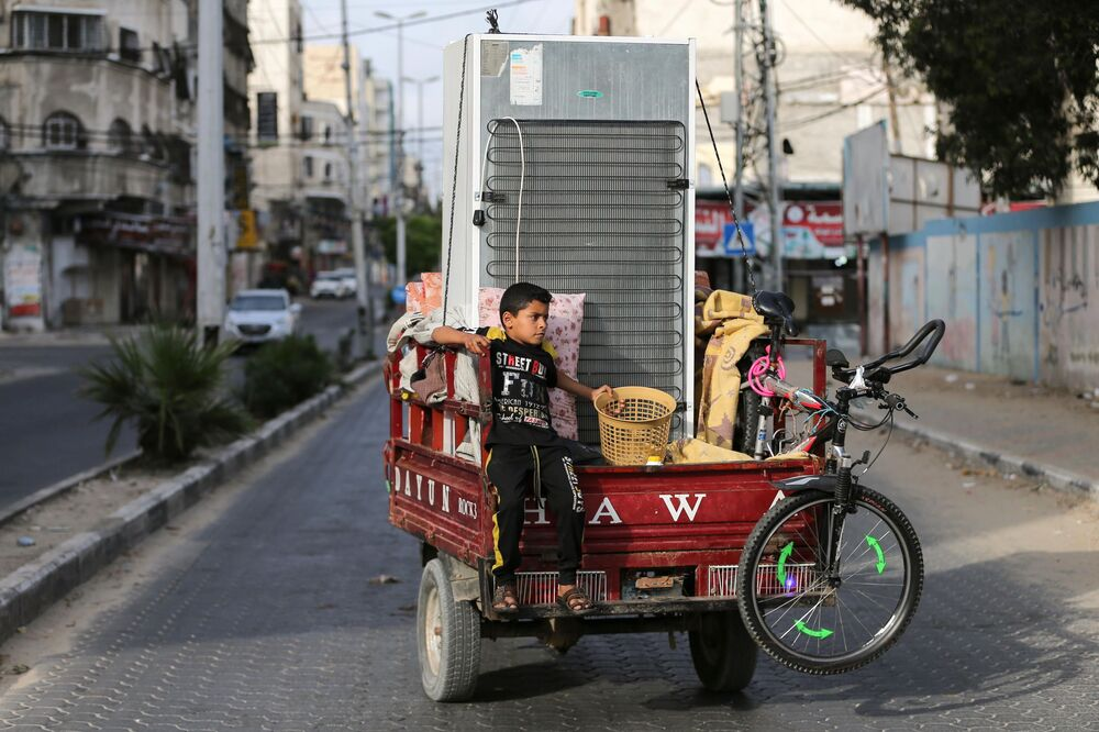 A Palestinian boy riding on an auto rickshaw loaded with his family's belongings heads to their home as he leaves a United Nations-run school where they took refuge during the recent cross-border violence between Palestinian militants and Israel, following the Israel-Hamas truce in Gaza.