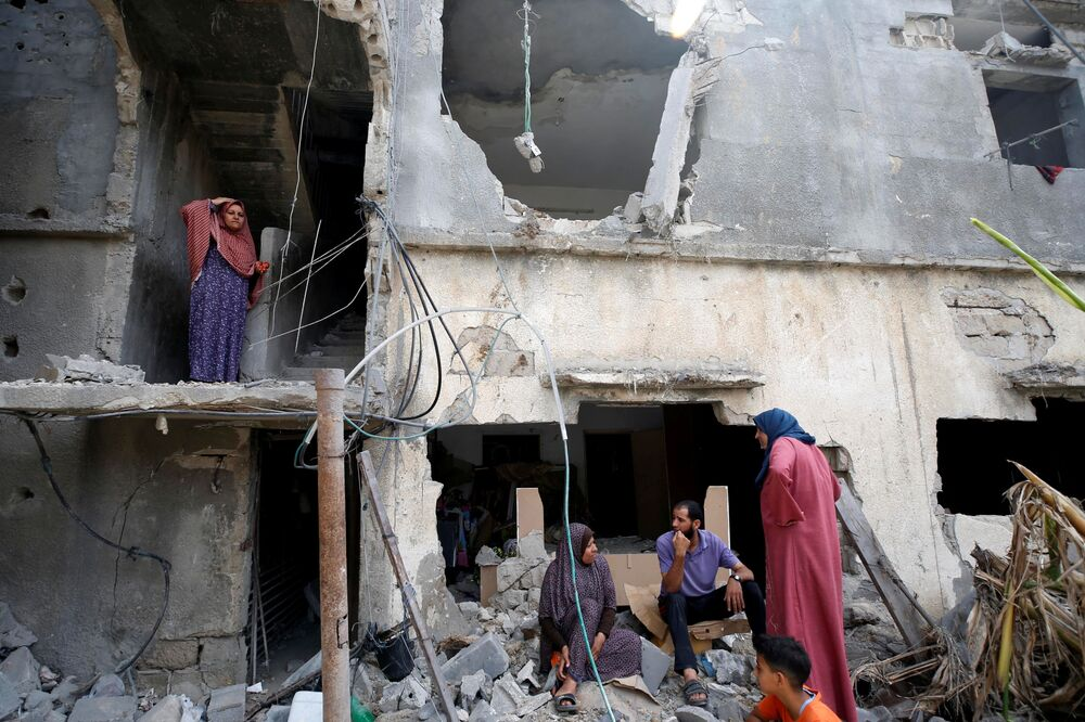Palestinians sit on debris after returning to their destroyed house following the Israel-Hamas truce, in Beit Hanoun in the northern Gaza Strip.