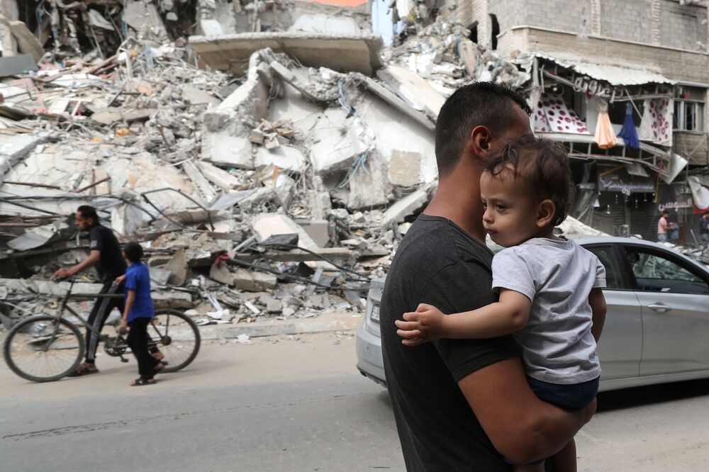 A Palestinian man carries a child as he walks past the ruins of a building destroyed in an Israeli airstrike in the recent cross-border violence between Hamas and Israel, in Gaza.