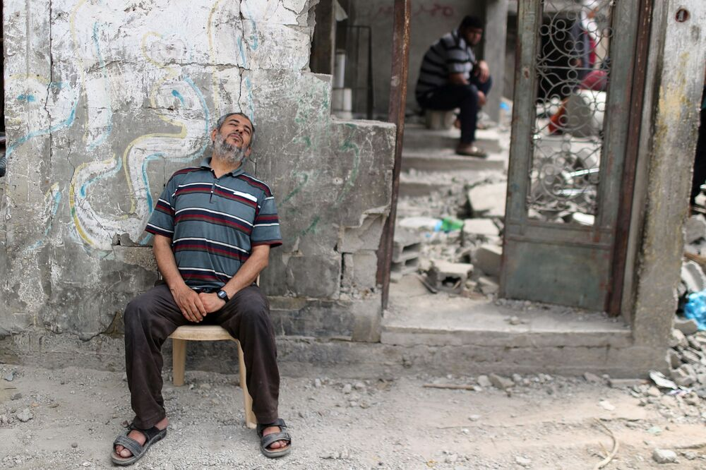 A Palestinian man rests after returning to his damaged house following the Israel-Hamas truce, in Beit Hanoun in the northern Gaza Strip.