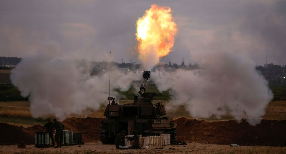 Israeli soldiers work at an artillery unit as it fires near the border between Israel and the Gaza strip, on the Israeli side May 17, 2021