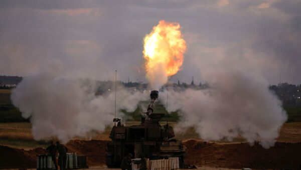 Israeli soldiers work at an artillery unit as it fires near the border between Israel and the Gaza strip, on the Israeli side May 17, 2021 - Sputnik International