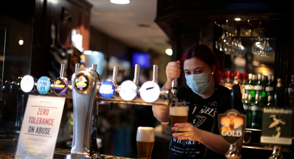 A woman pours a pint at The Fox on the Hill pub which has reopened as coronavirus disease (COVID-19) restrictions continue to be eased, in Denmark Hill, London, Britain, 17 May 2021.