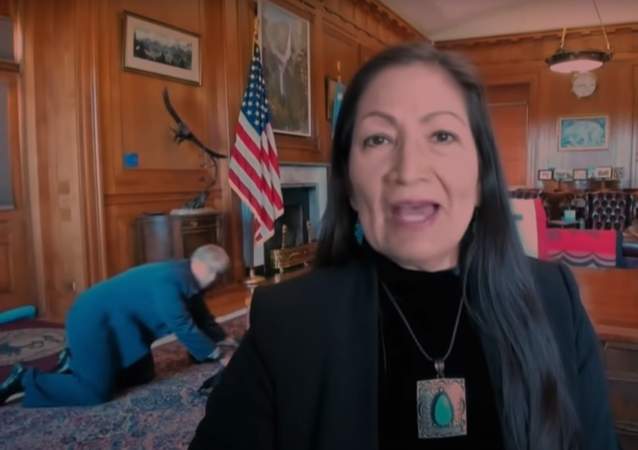 Late Night With Seth Meyers video clip screenshot showing a staffer crawling on the floor behind US Secretary of Interior Deb Haaland during the interview