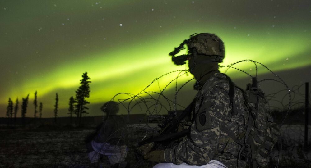In this Oct. 25, 2016 photo provided by the U.S. Army Alaska, paratroopers secure an area in view of the aurora borealis, or northern lights, during night live-fire training at Fort Greely, Alaska. The battalion spent much of Exercise Spartan Cerberus in subzero temperatures training in Arctic, airborne and infantry tasks.