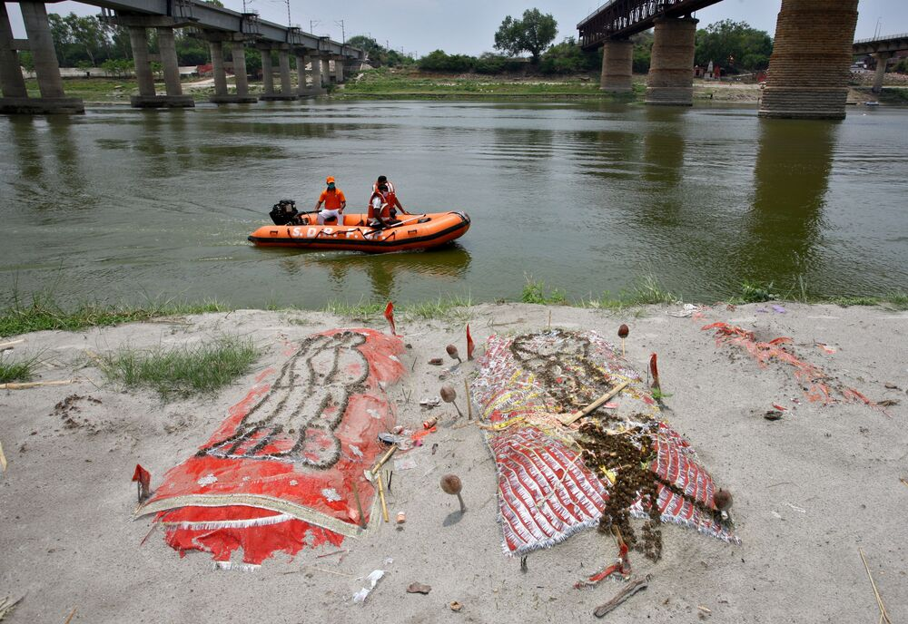 Members of the State Disaster Response Force (SDRF) patrol the Ganges River past shallow sand graves for people, some of whom are suspected to have died of the coronavirus disease (COVID-19), on the banks of the river Ganges in Phaphamau on the outskirts of Prayagraj, India, 21 May 2021.