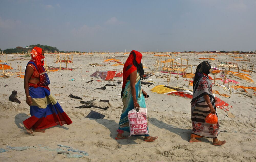 Women walk past shallow sand graves for people, some of whom are suspected to have died of the coronavirus disease (COVID-19), on the banks of the river Ganges in Shringaverpur on the outskirts of Prayagraj, India, 21 May 2021.
