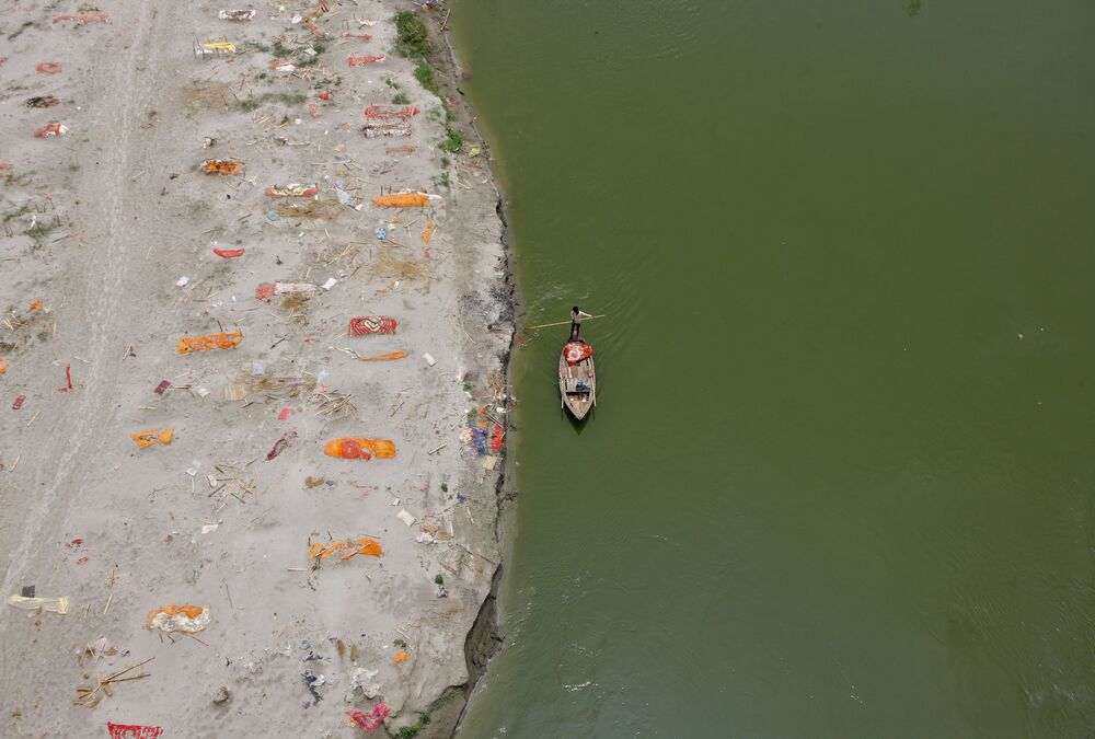 A man rows his boat past shallow sand graves for people, some of whom are suspected to have died of the coronavirus disease (COVID-19), on the banks of the Ganges River in Phaphamau on the outskirts of Prayagraj, India, 21 May 2021.