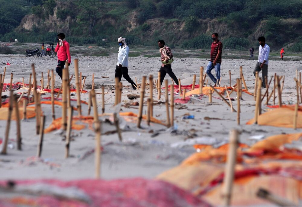 Men walk past shallow sand graves for people, some of whom are suspected to have died of the coronavirus disease (COVID-19), on the banks of the Ganges River in Phaphamau on the outskirts of Prayagraj, India, 21 May 2021.