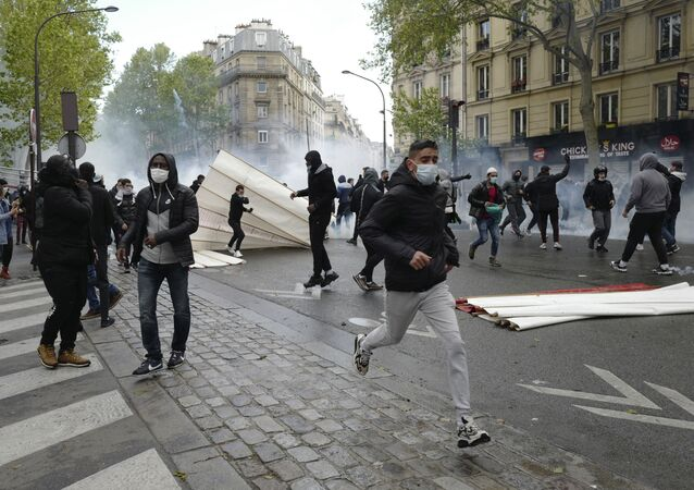 Youths run away during a banned protest in support of Palestinians in the Gaza Strip, in Paris, Saturday, May, 15, 2021.