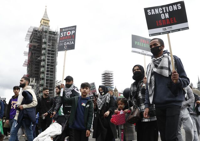 Protesters hold placards and banners in London, Saturday, May 22, 2021, as they take part in a rally supporting Palestinians.