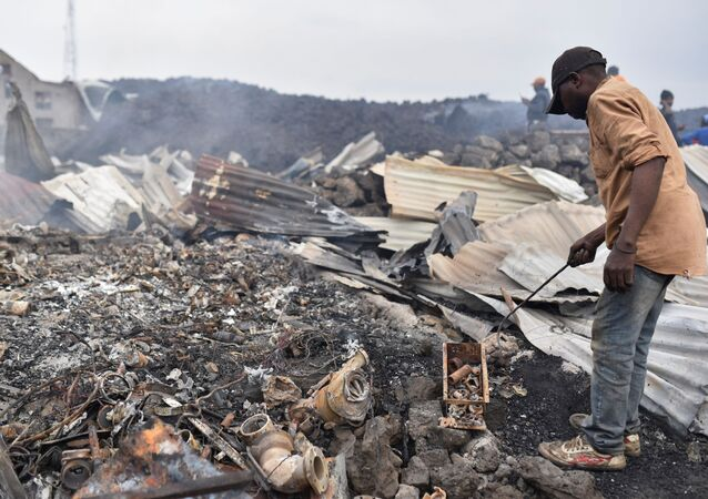 Residents pick up remains of their destroyed homes from the smouldering lava deposited by the eruption of Mount Nyiragongo volcano near Goma, in the Democratic Republic of Congo May 23, 2021.