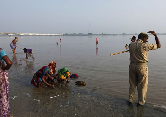 An Indian policeman, right, alongside Hindu women perform rituals by the Sarayu River in Ayodhya, about, 550 kilometers (350 miles) east of New Delhi, India, Sunday, Aug. 25, 2013
