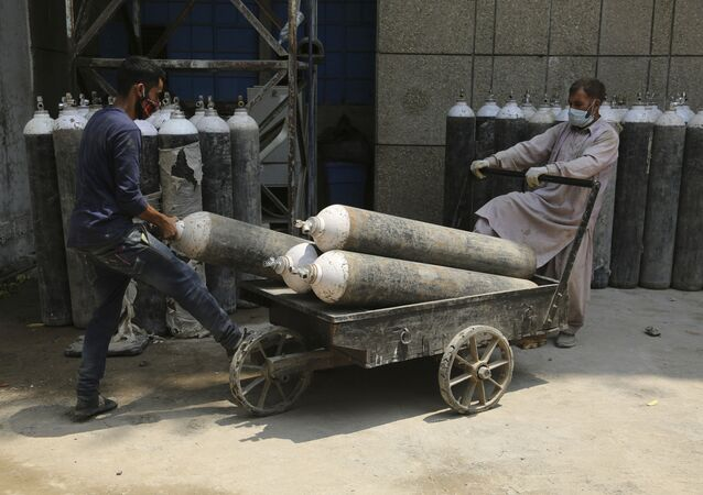 Workers load oxygen cylinders onto a hand cart to be carried inside the COVID-19 wards at a government-run hospital in Jammu, India, Friday, 7 May 2021