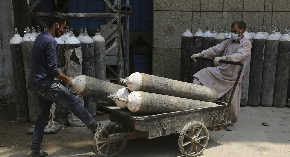 Workers load oxygen cylinders onto a hand cart to be carried inside the COVID-19 wards at a government run hospital in Jammu, India, Friday, May 7, 2021