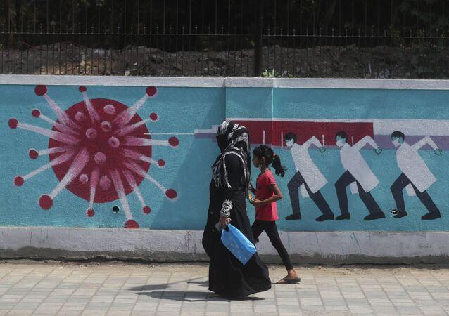 A woman along with a girl walk past a graffiti, depicting the coronavirus in Mumbai, India, Tuesday, April 6, 2021