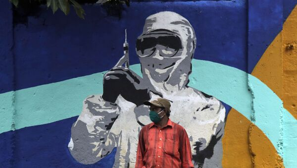 A man stands in front of a graffiti honoring those in the frontlines in the fight against the coronavirus in Mumbai, India, Tuesday, July 7, 2020 - Sputnik International