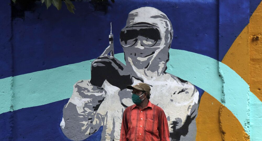 A man stands in front of a graffiti honoring those in the frontlines in the fight against the coronavirus in Mumbai, India, Tuesday, July 7, 2020
