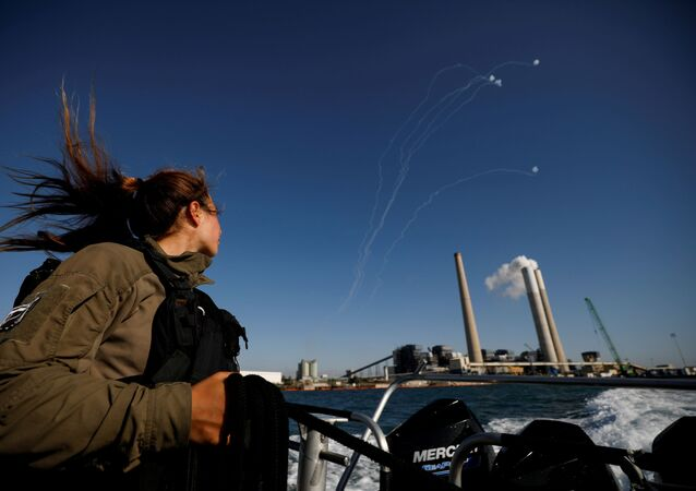 An Israeli soldier looks on as Israel's Iron Dome anti-missile system intercept rockets launched from the Gaza Strip towards Israel, as it seen from a naval boat patrolling the Mediterranean Sea off the southern Israeli coast as Israel-Gaza fighting rages on May 19, 2021
