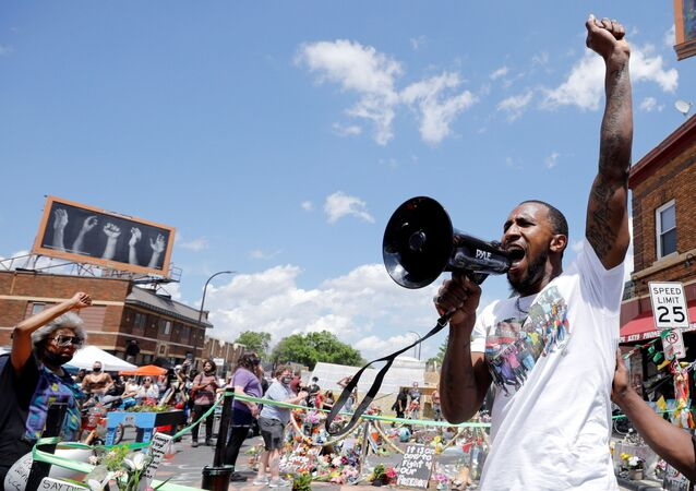 Community organizer Tommy McBrayer leads a chant in solidarity with George Floyd on the first anniversary of his death, at George Floyd Square, in Minneapolis, Minnesota, U.S., May 25, 2021.