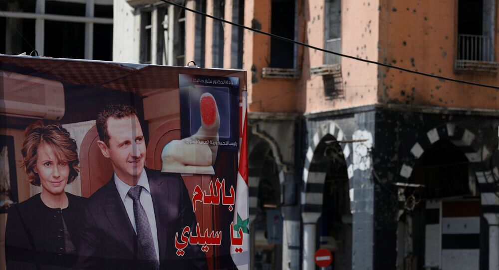 A view shows a banner depicting Syria's President Bashar al-Assad and his wife Asma, near a damaged building, ahead of the May 26 presidential election, in Homs, Syria May 23, 2021.