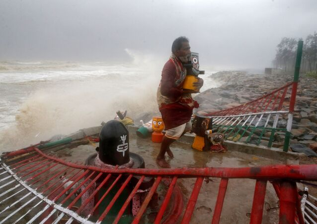 A Hindu priest carries an idol of Lord Jagannath from a seafront temple to a safer place ahead of Cyclone Yaas in Balasore district in the eastern state of Odisha India, May 26, 2021