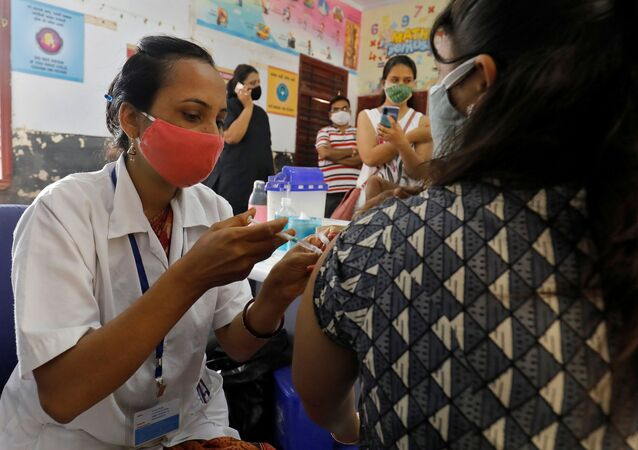 A healthcare worker gives a woman a dose of coronavirus disease (COVID-19) vaccine Covishield, made by the Serum Institute of India, inside the classroom of a school which has been converted into a temporary vaccination centre, in Ahmedabad, Gujarat state, India on 1 May 2021.