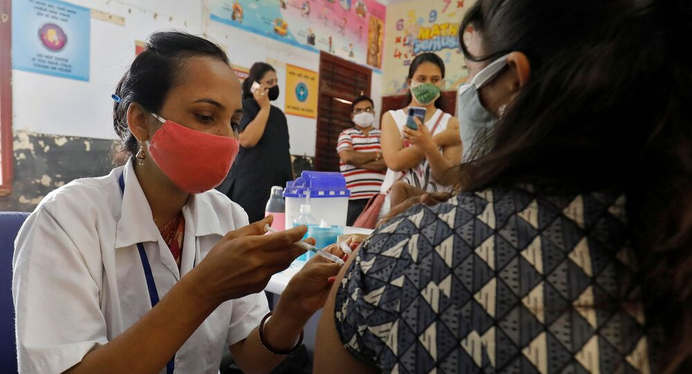 A healthcare worker gives a dose of COVISHIELD, a coronavirus disease (COVID-19) vaccine manufactured by Serum Institute of India, to a woman inside a classroom of a school, which has been converted into a temporary vaccination centre, in Ahmedabad, India, May 1, 2021
