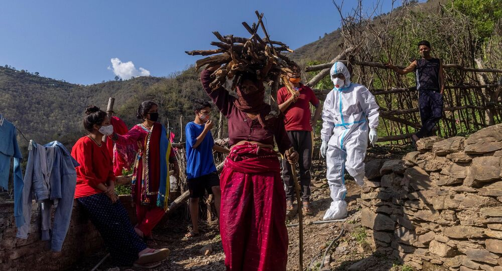 A healthcare worker wearing personal protective equipment (PPE), arrives to collect swabs from villagers to test them for COVID-19 (File)