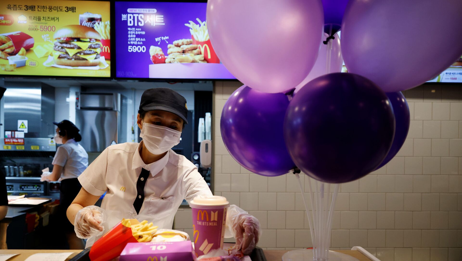 An employee of McDonald's serves a BTS meal, which is inspired and promoted by K-pop boy band BTS, during lunch hour at its restaurant in Seoul, South Korea, May 27, 2021 - Sputnik International, 1920, 28.07.2021