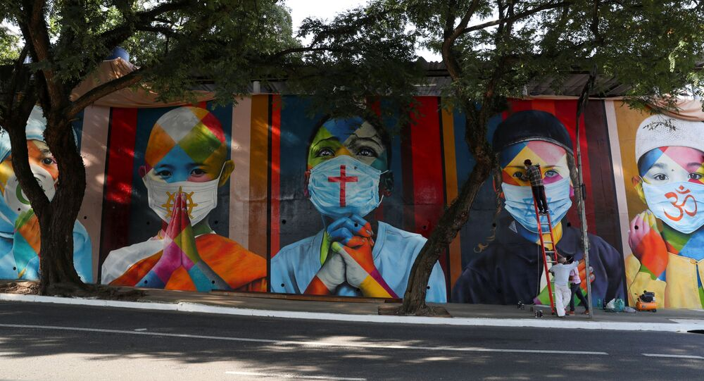 Brazilian graffiti artist Eduardo Kobra puts the final touches to his mural 'Coexistencia – Memorial da Fe por todas as vitimas do Covid-19', translated as 'Coexistence - Memorial of Faith for all victims of Covid-19', which portrays children of different religions wearing protective face masks, in Sao Paulo, Brazil May 5, 2021
