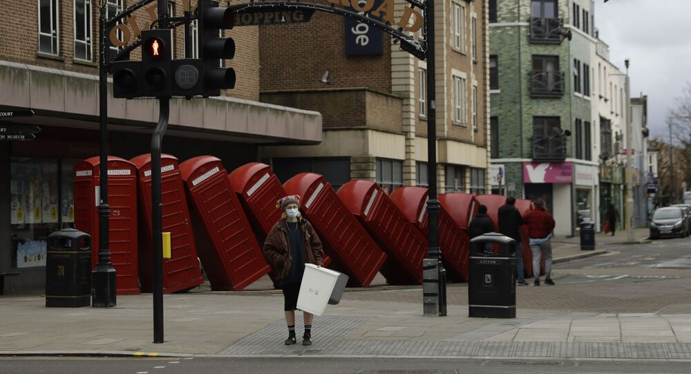 A woman wearing a face mask to curb the spread of coronavirus waits to cross the street backdropped by Out of Order a 1989 red phone box sculpture by British artist David Mach, in Kingston upon Thames, south west, London, Tuesday, Jan. 19, 2021
