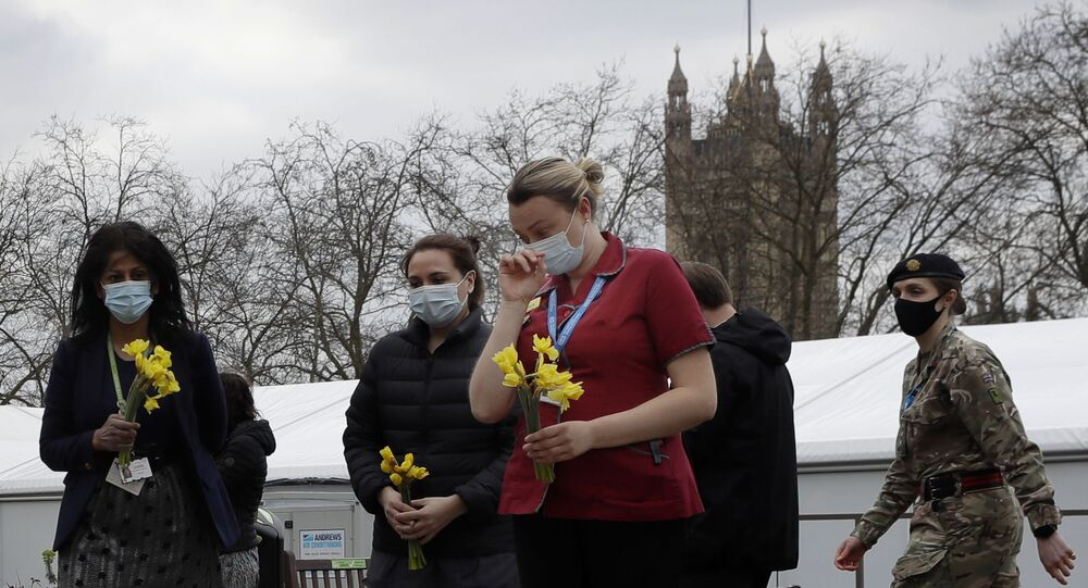 Members of NHS staff lay flowers after a minute of silence and reflection at St Thomas' hospital in London, Tuesday, March 23, 2021