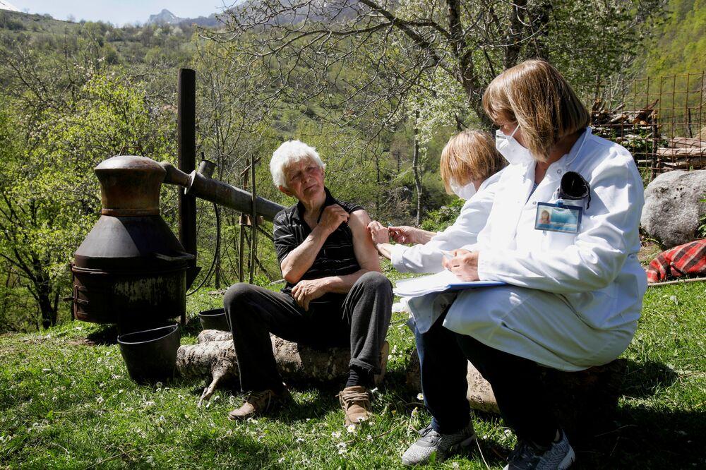 A man receives a coronavirus vaccine next to a brandy pot still in the remote mountain village of Ljevista in Kolasin municipality, Montenegro.