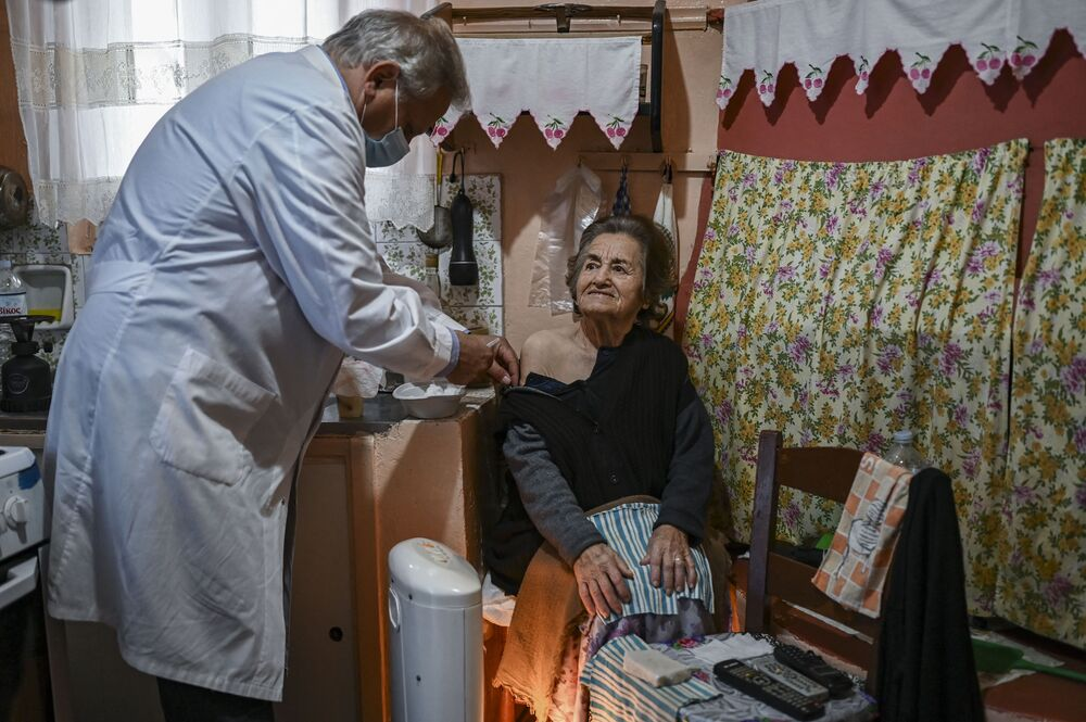 Doctor Anargyros Mariolis (R) vaccinates an elderly woman against COVID-19 who is unable to visit a health centre in Elafonissos, on Elafonissos Island.
