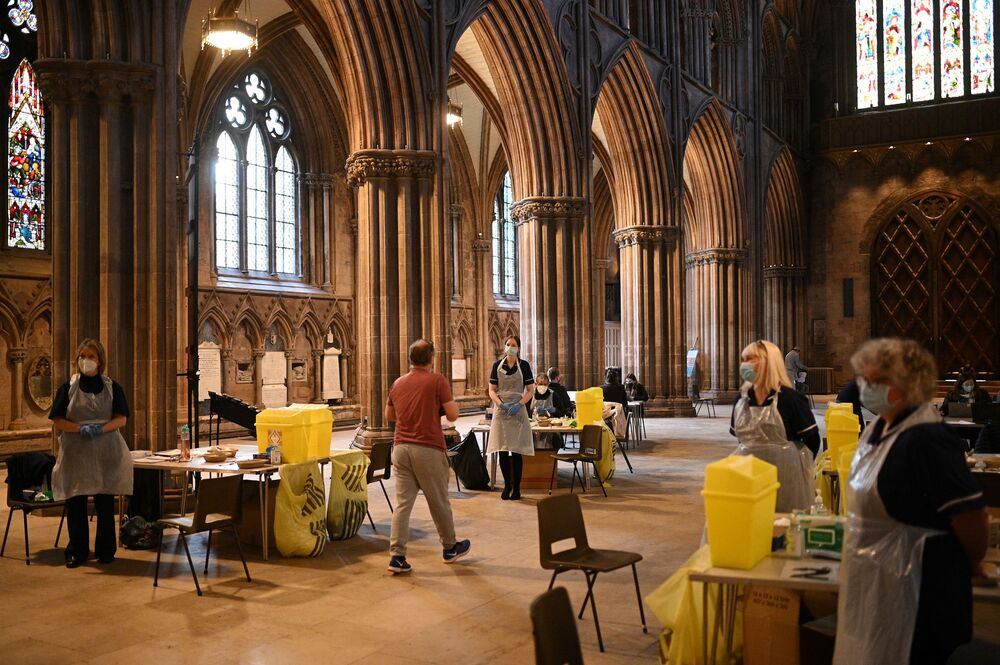 Members of the public receive a dose of the Oxford/AstraZeneca COVID-19 vaccine at Lichfield cathedral, which has been converted into a temporary vaccination centre, in Lichfield, central England.
